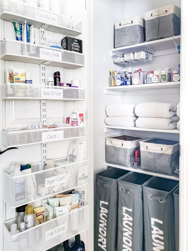 white organized linen closet with organization on the door and gray bins on the shelves.