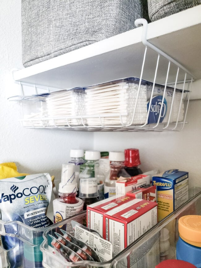 Q-Tip containers in under shelf bin above medicine