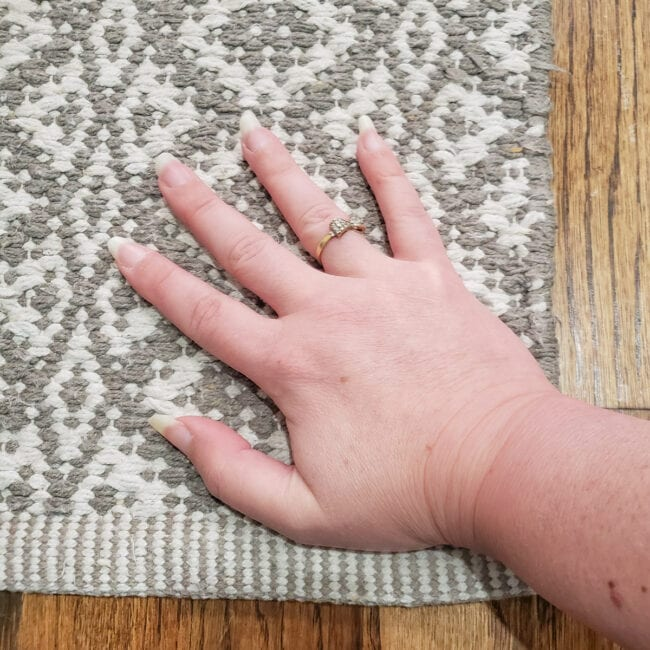 Hand pressng corner of grey and white rug