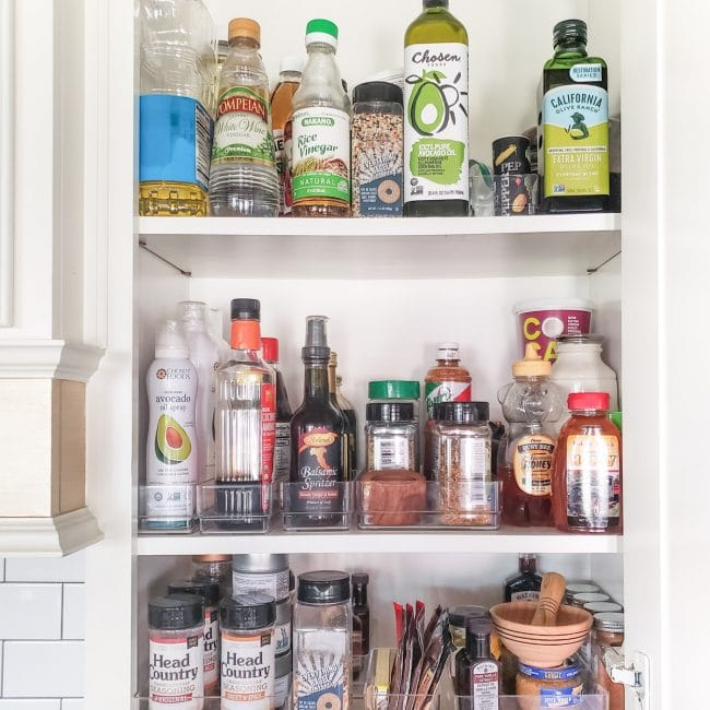 White cabinet full of cooking items like spices, oils, and vinegars