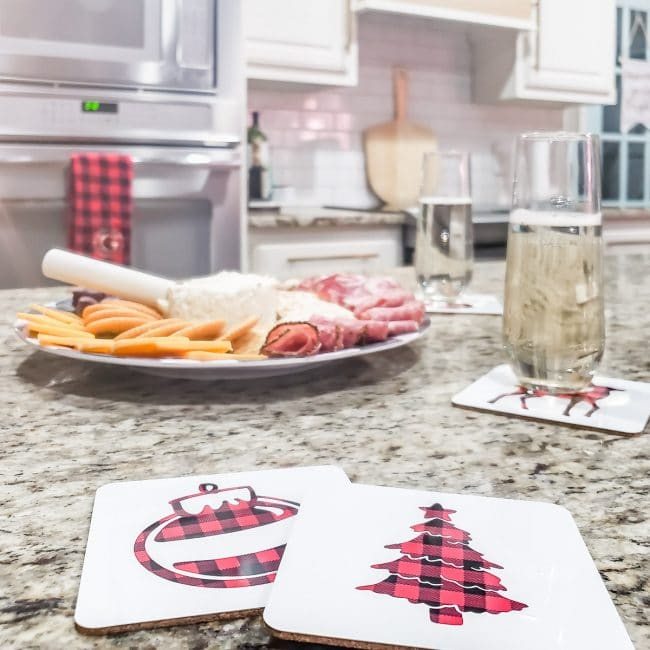 white coasters with buffalo check tree and ornament on granite kitchen counter