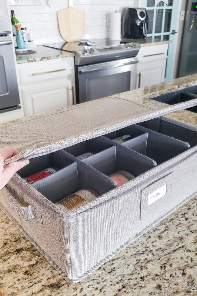 Grey divided container holding candles on kitchen counter