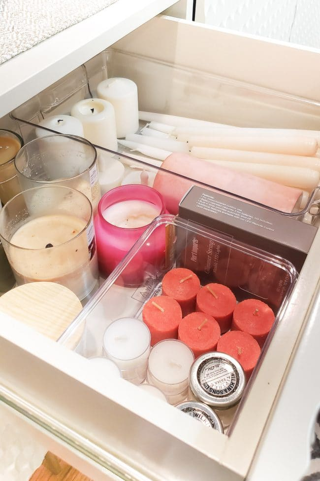 Drawer with various candles seperated into clear bins