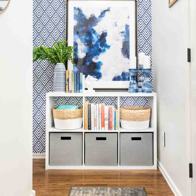 Hallway with wood floors, and white cube storage organizer against geometric blue and white wall. Organizer filled with bins and books.