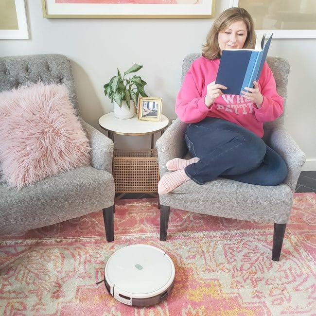 girl in pink shirt reading book in grey chair while white robot vacum cleans the floor