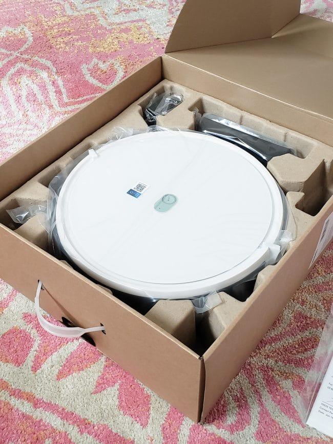 cardboard box with white, circular robot vacuum inside