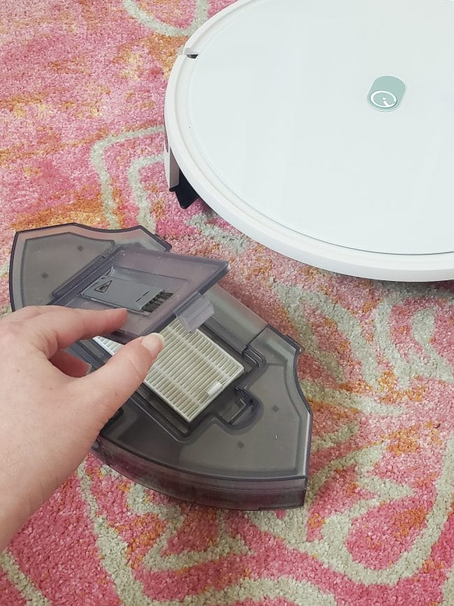 opening gray flap in plastic container to expose vacuum filter
