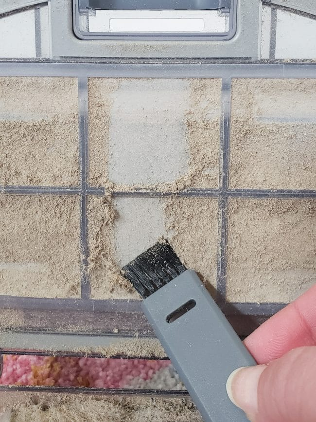 Using small nylon brush to clean vacuum filter