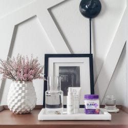 Wood nightstand with marble tray containing clear water carafe & bottle of Natrol Vitamins next to white vase with pink flowers