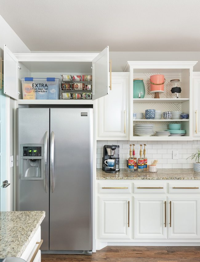 white cabinets & stainless steel fridge with cabine above the fridge open & canned goods inside